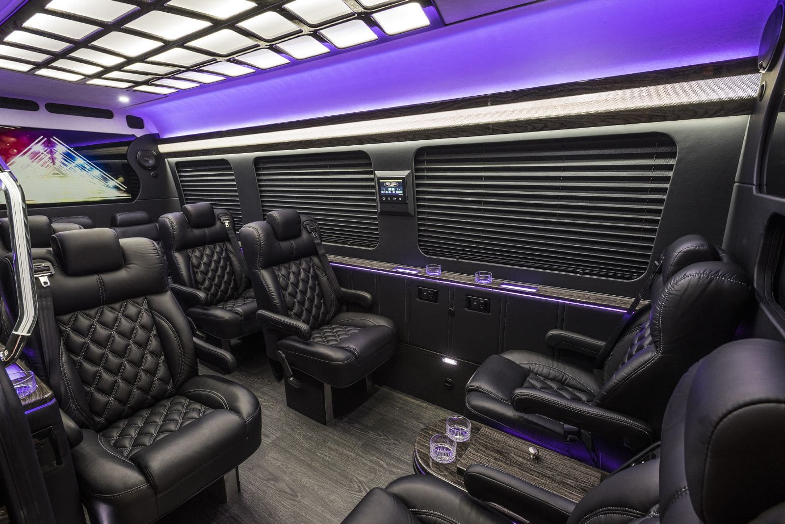Spacious, black leather interior of the Mercedes Jet Sprinter ready for corporate transporation.