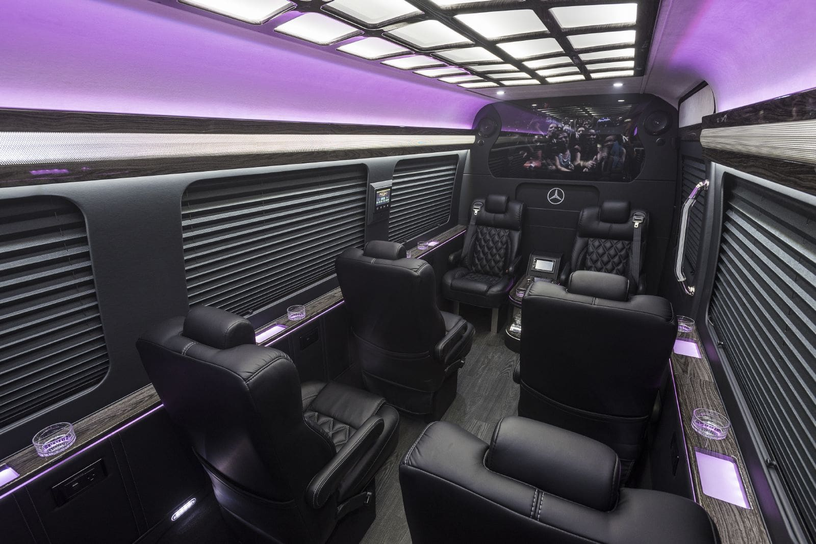 Spacious interior of the Mercedes Jet Sprinter showing the leg room, drink cooler, and outlets for the perfect corporate limo rental.