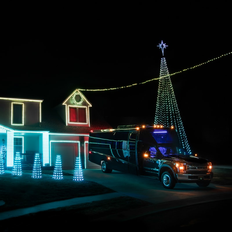 A Kansas City Christmas Light Show with our Grech Mini Coach beside it, representing the fact that Prestige Transportation takes you to all the best spots.