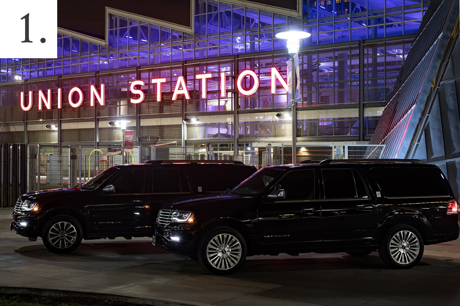 Two black Lincoln Navigator luxury SUVs in front of Union Station.